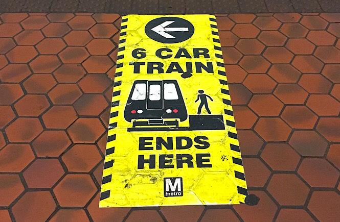 """Photo of a floor sticker that reads, """"6 car train ends here."""""""