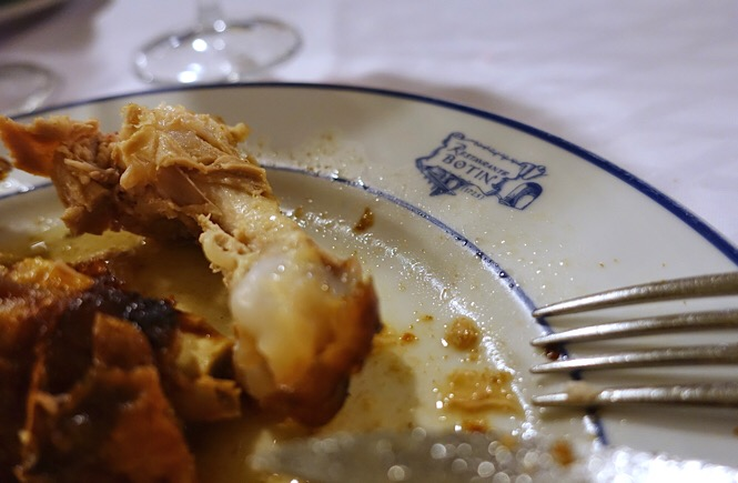 Photo of suckling pig bones and a fork on the corner of a plate bearing the Botin logo.