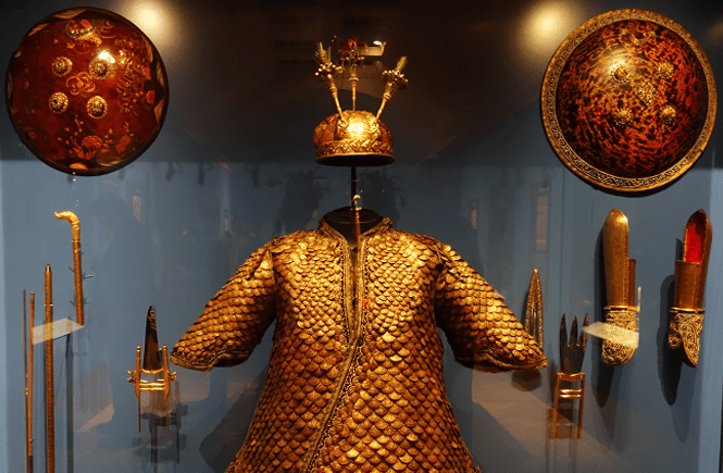 Photo of an armored suit, swords, helmet, and shield from India.
