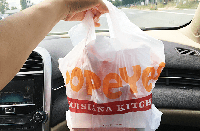 Photo of a Popeyes bag filled with two chicken sandwich meals.