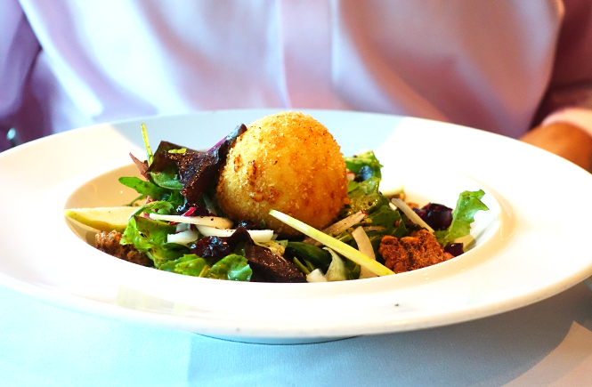 Photo of a bowl of warm goat cheese salad from Chops Grille on Royal Caribbean Enchantment of the Seas cruise ship by Frolic & Courage.