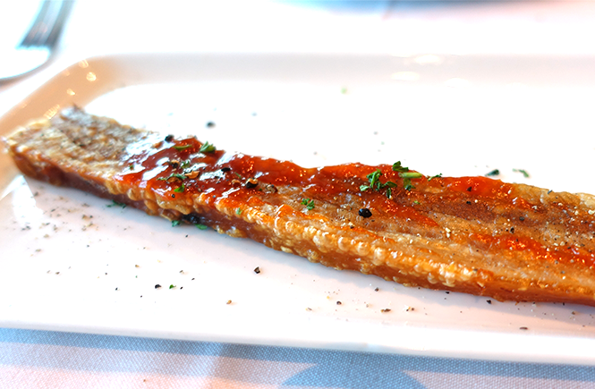 Photo of a plate containing a thick strip of grilled black pepper bacon from Chops Grille on Royal Caribbean Enchantment of the Seas cruise ship by Frolic & Courage.