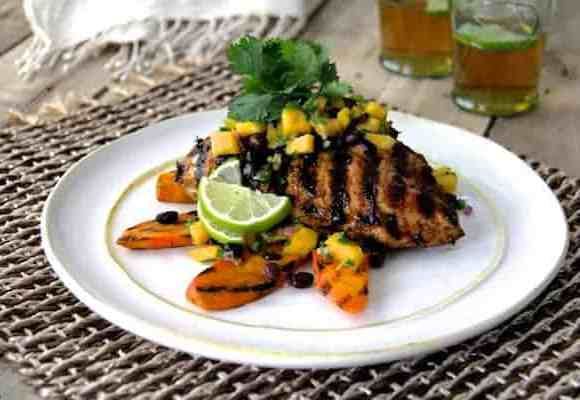 Jamaican Jerk Style Chicken with Black Bean Mango Salsa - Topped with grilled sweet potatoes, garnished with cilantro and lime wedges on a white plate on rattan placemat. Beer in the background!