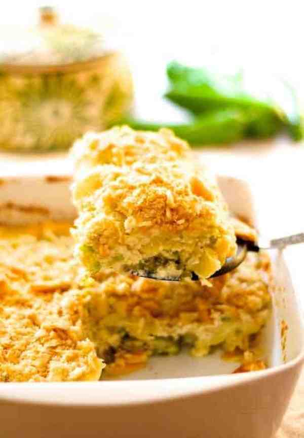 Southwestern Summer Squash Casserole - Hero shot of casserole in white baking dish with a serving being lifted from the dish