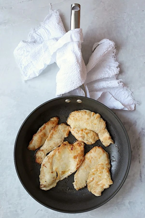 Overhead shot of turkey scallopini in large nonstick skillet that has been browned on both sides