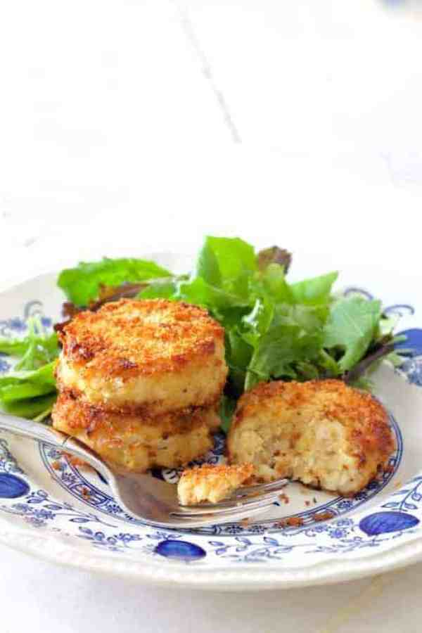 Maryland-Style Crab Cakes - Crab cakes and baby greens on blue patterned plate with crab cake cut into with some on the fork