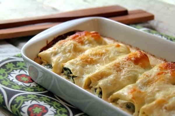 Chicken Spinach and Artichoke Cannelloni - In white baking dish on green printed towel