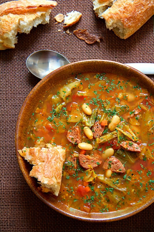 Farmhouse Cabbage Soup with Cannellini Beans and Kielbasa - Overhead hero shot of soup in brown bowl on purple background with bread scattered around