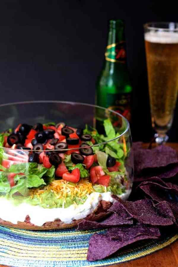 Healthier 7-Layer Dip - Dip in glass serving bowl on colorful placemat with chips scattered around the bowl and beer in the background