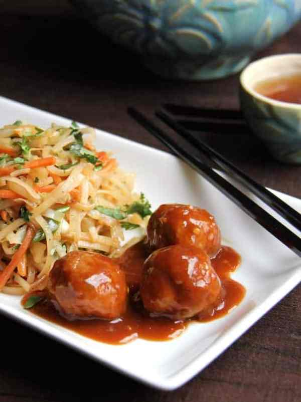 Hoisin Glazed Pork Meatballs and Rice Noodles with Cabbage and Carrots - On white rectangular plate with black chopsticks and blue teapot in the background