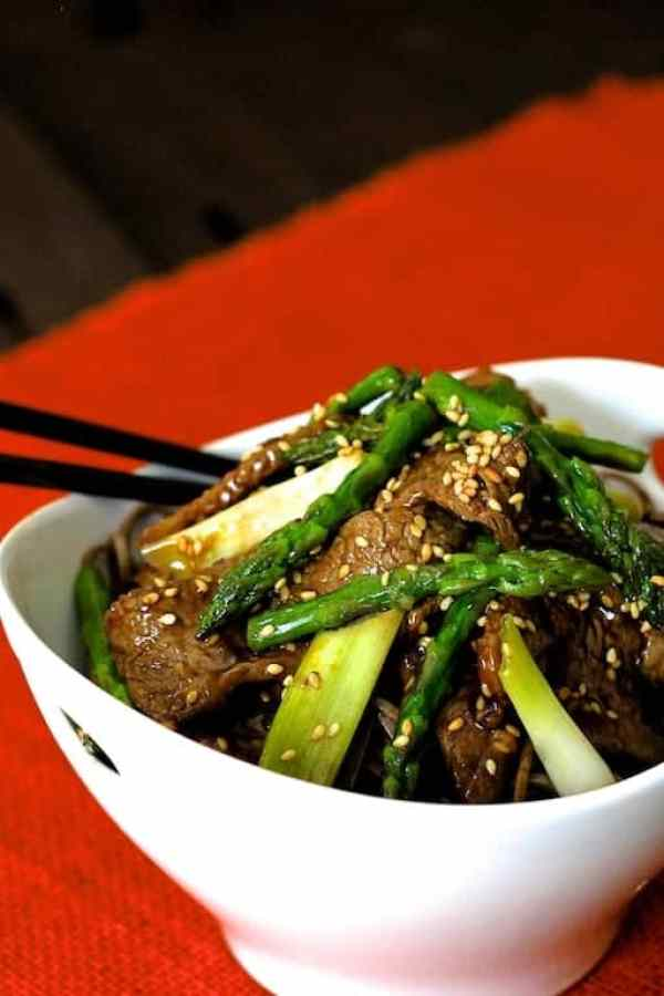 Sesame Beef and Asparagus Stir Fry - Hero shot of dish in white bowl garnished with sesame seeds on red placemat