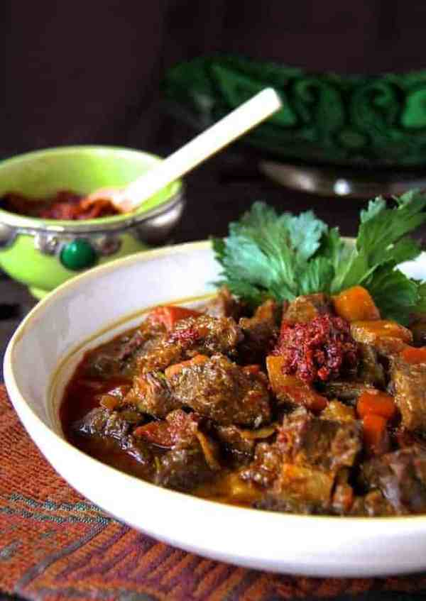 Moroccan Beef Stew with Harissa - Stew in white bowl garnished with celery leaves and harissa