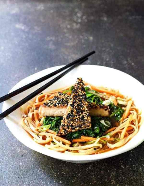 Sesame Tofu with Spinach and Rice Noodles in Ginger Broth - In white bowl with chopsticks on gray background