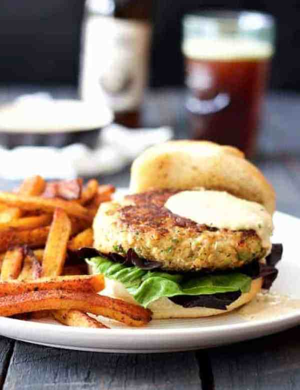 Shrimp Burgers with Jalapeño Remoulade - Hero shot of burgers with sweet potato fries on white plate with beer in the background