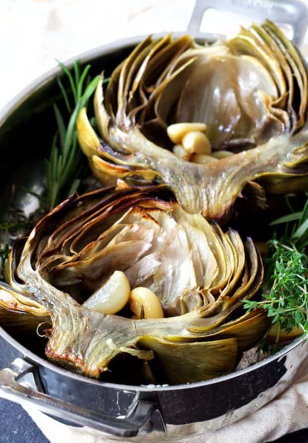 Oven Roasted Artichokes with Roasted Garlic Butter close-up shot in roasting pan with herb sprigs