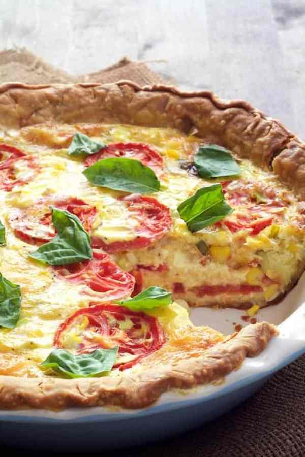 Tomato and Corn Pie with Fresh Basil - Shot of quiche with a piece served to expose interior