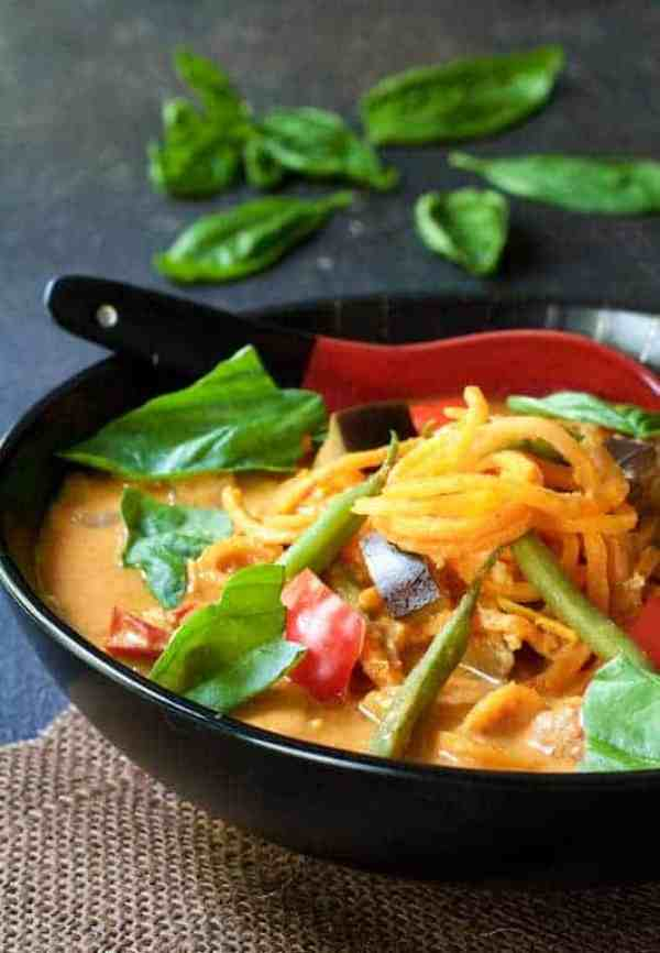 Thai Red Curry with Vegetables and Sweet Potatoes - In black bowl on brown burlap garnished with fresh basil