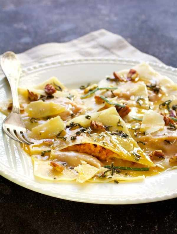 Pumpkin Ravioli with Sage Brown Butter Parmesan and Pecans - Shot of ravioli after butter is poured with one of the ravioli cut into