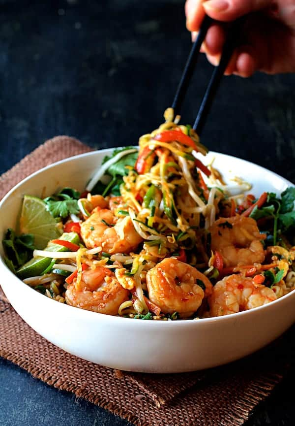 Shrimp Pad Thai with Zucchini Noodles - Finished dish in white bowl on brown burlap with zucchini noodles being pulled up out of the bowl with chopsticks
