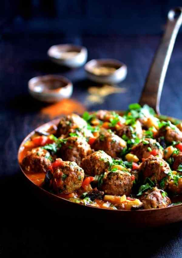 Moroccan Meatball and Vegetable Ragout - Shot of ragout in skillet garnished with cilantro with spice bowls in the background