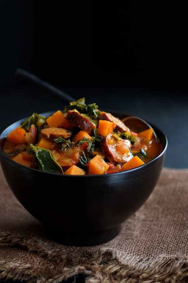 Chorizo Kale and Sweet Potato Stew - Hero shot of stew in black bowl on brown burlap