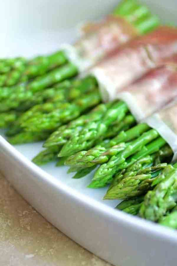 Asparagus Cordon Bleu - Asparagus in baking dish wrapped in prosciutto before cheese and breadrumbs are added.
