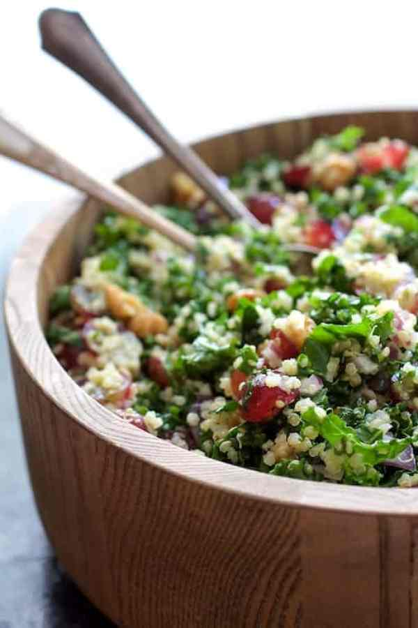 Quinoa and Kale Salad with Red Grapes, Walnuts and Honey - Lemon Dressing - Close-up straight-on shot of salad in wooden bowl