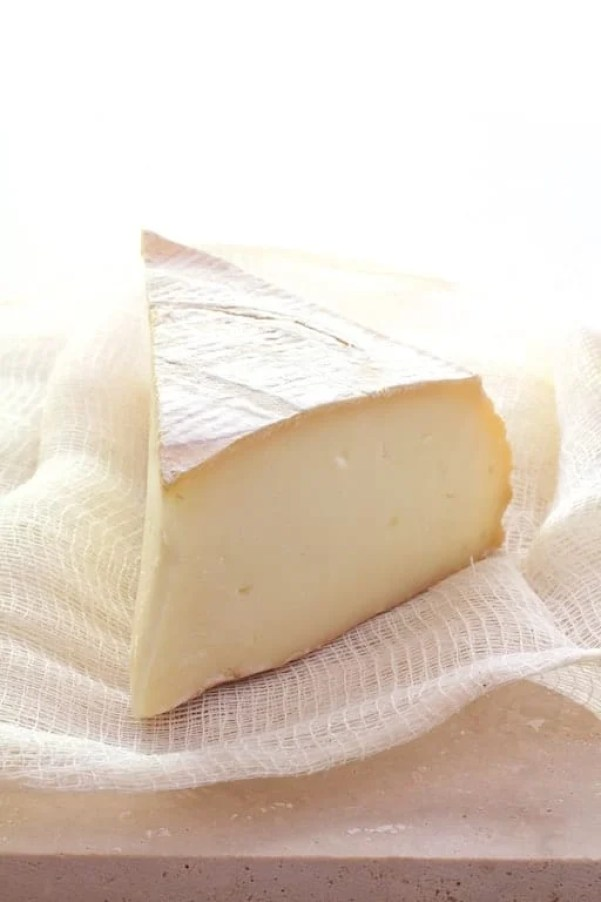 Wedge of Tallegio cheese on white cheesecloth
