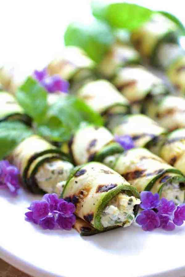 Cheese and Artichoke Stuffed Tomatoes and Grilled Zucchini - Finished rolled zucchini garnished with violets