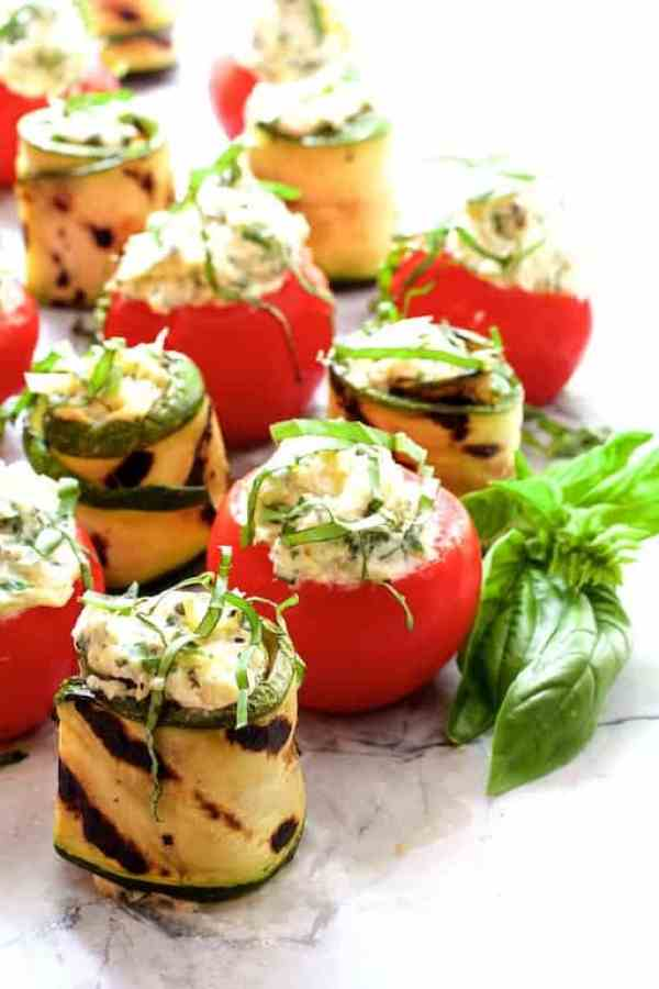 Cheese and Artichoke Stuffed Tomatoes and Grilled Zucchini - Another shot of appetizer on marble surface garnished with fresh basil sprig