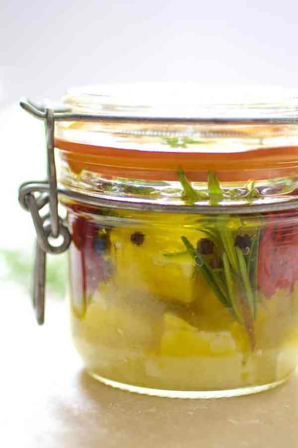 Side view of jar of marinated feta cheese