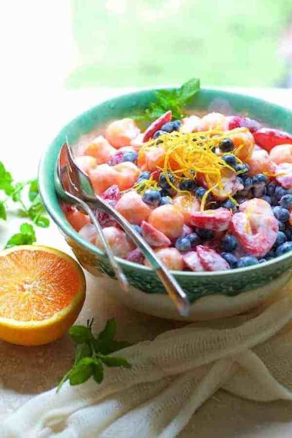 Summer Fruit Salad with Orange Vanilla Yogurt Dressing in green and white bowl garnished with orange zest and mint sprigs