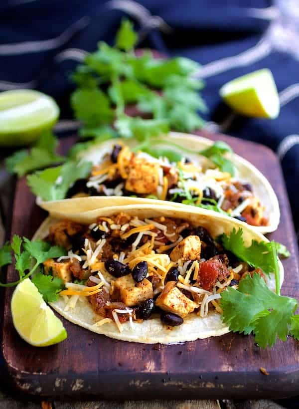 Tofu and Black Bean Tacos - Straight-on shot of tacos on wood surface garnished with lime wedges and cilantro