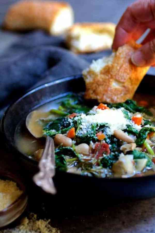 Cannellini Bean, Artichoke and Baby Greens Soup - Soup with bread being dipped into it