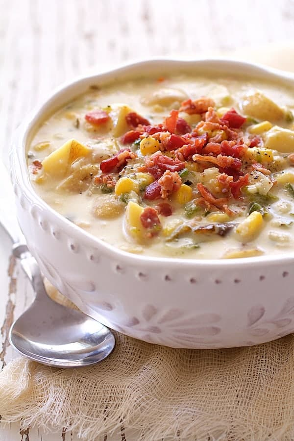Roasted Poblano, Corn and Potato Chowder with Bacon and Gouda Cheese - Close-up straight-on shot of soup in white bowl with spoon on the side