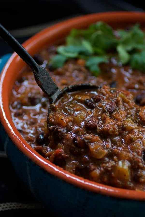Spoonful of chili being lifted out of bowl with cast iron ladle