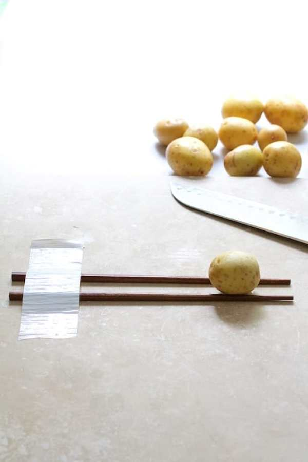 Process shot of baby Yukon Gold potato sitting on two chopsticks before being hasselbacked