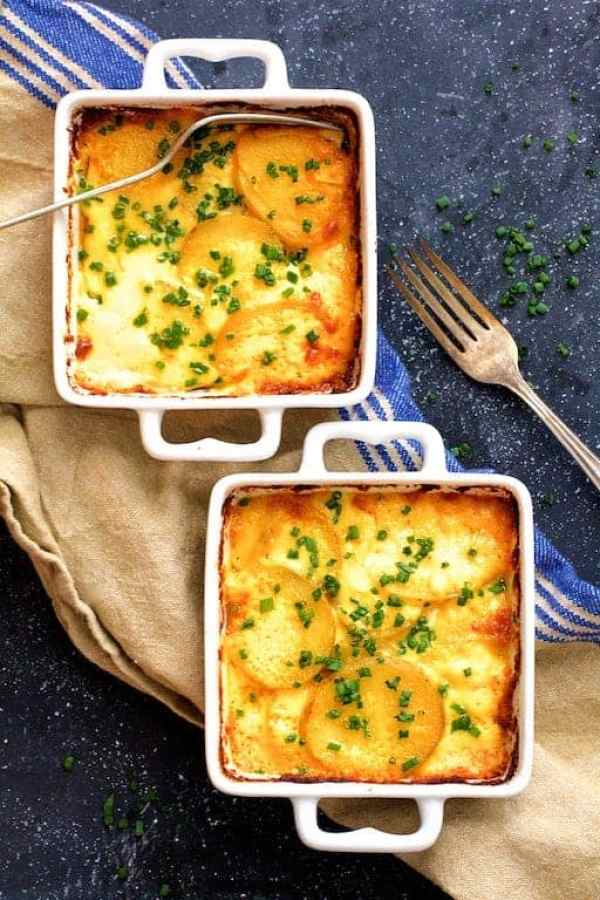Au Gratin Potatoes for Two - Overhead shot of potatoes in individual baking dishes on blue background