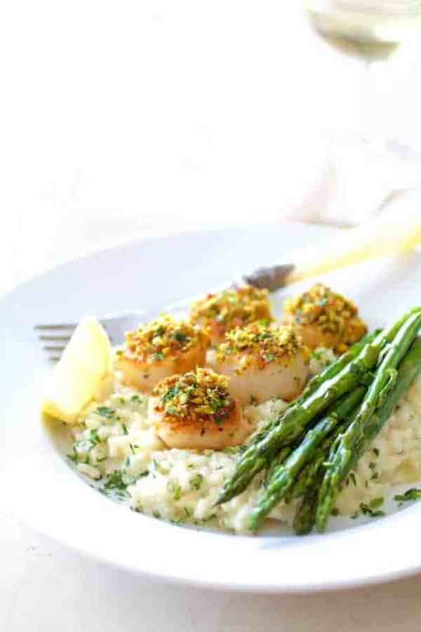 Pistachio Encrusted Sea Scallops with Champagne Risotto and Roasted Asparagus - On white plate garnished with lemon wedge and wine glass in background