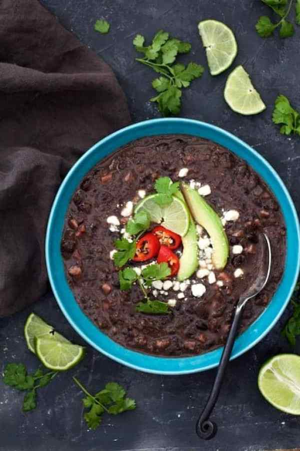 Slow Cooker Black Bean Soup with Ham - Overhead shot of soup in blue bowl garnished with lime wedges, cilantro and avocado