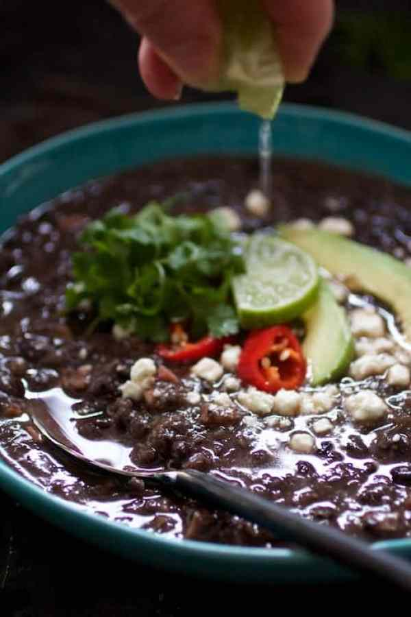 Slow Cooker Black Bean Soup with Ham - Lime juice being squeezed over a bowl of the soup