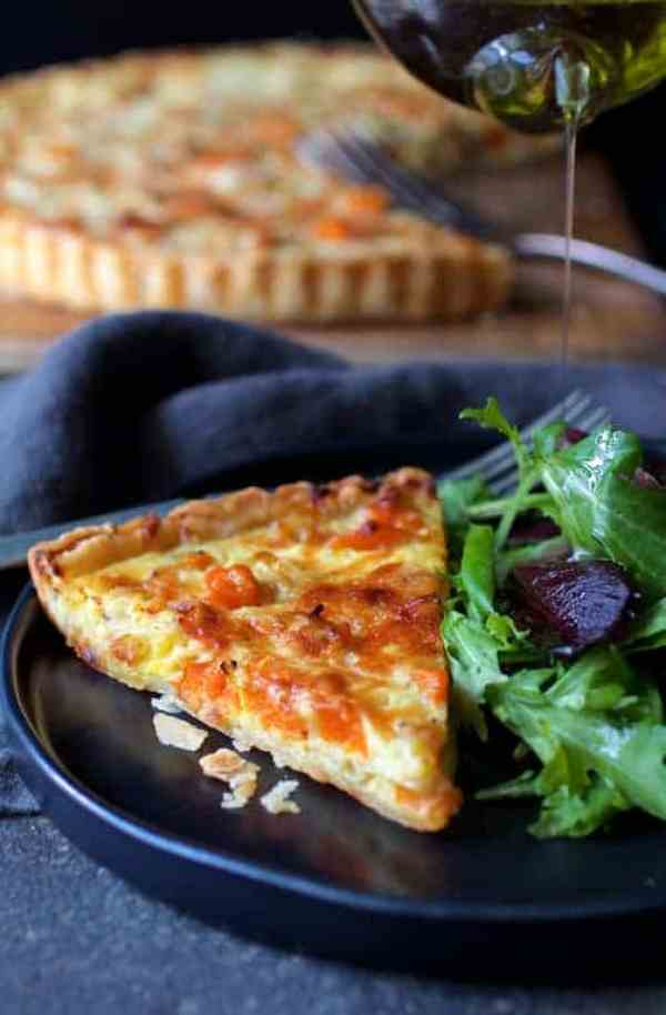 Butternut Squash Leek and Gruyere Tart - One piece of the tart on black plate with salad being drizzled with olive oil