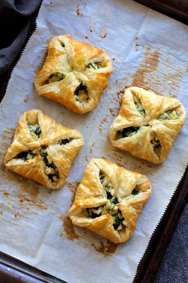 Overhead shot of baked Chicken, Spinach and Artichoke Puff Pastry Parcels on parchment paper-lined baking sheet