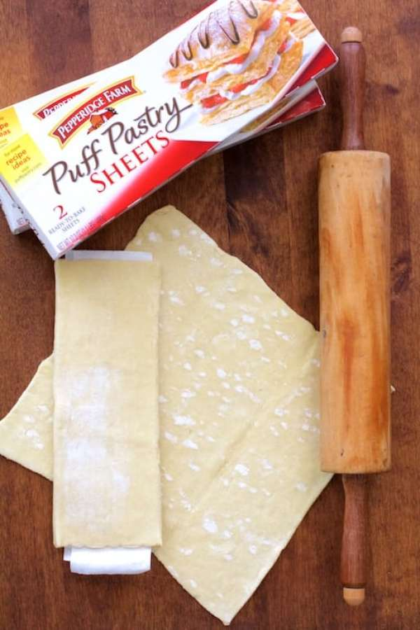Two boxes of puff pastry plus the puff pastry sheets on wood cutting board with rolling pin