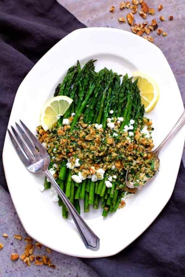 Roasted Asparagus with Goat Cheese and Walnut Lemon Gremolata - Overhead shot on white platter with gray napkin and walnuts scattered around