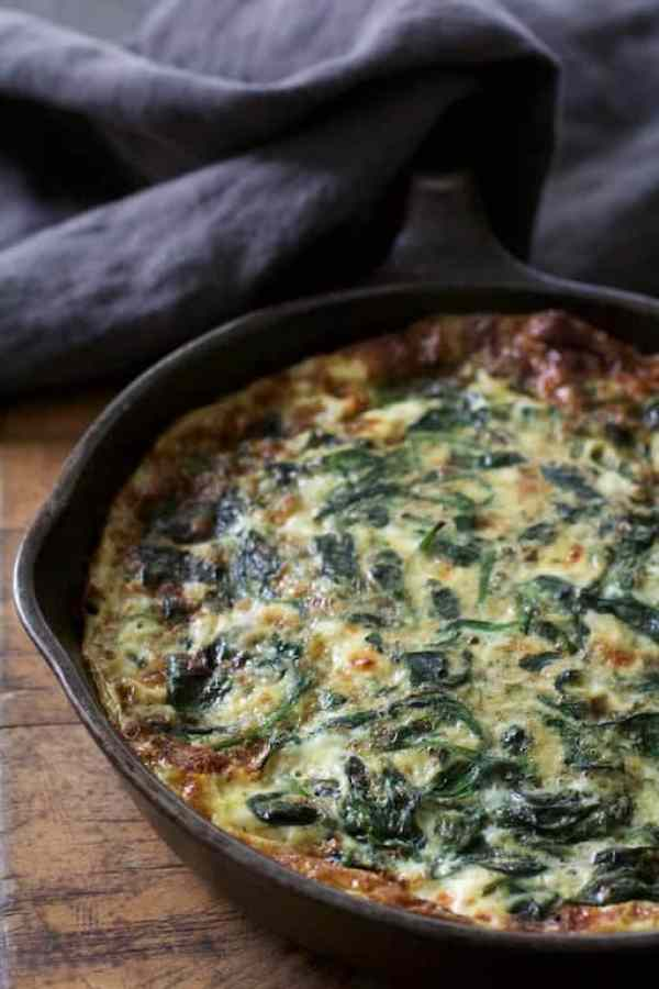 Spinach Leek and Feta Cheese Frittata - Straight-on shot in cast iron skillet with gray towel over handle