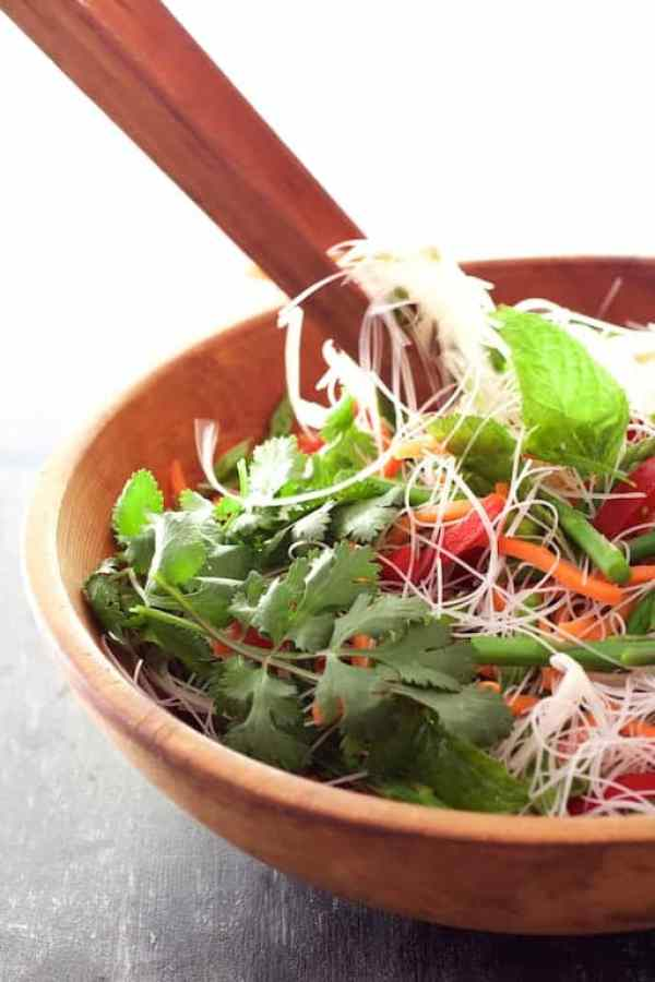 Vietnamese Spring Roll Salad being tossed together with wooden tongs