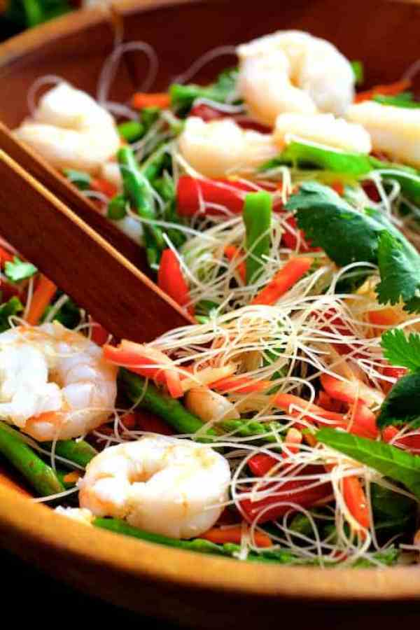Vietnamese Spring Roll Salad - Salad being tossed together in wooden bowl with wooden tongs