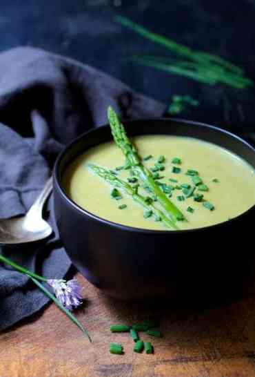 Cream of Asparagus and Ramp Soup with Curry close-up with chives and chive blossom