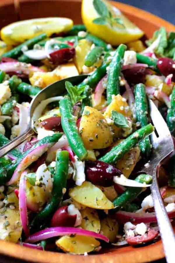 Potato Green Bean Salad with Olives and Feta Cheese - Close-up shot of salad being served with serving spoon and fork